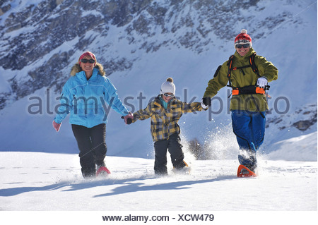 family on winter vacation happily walking through a snowy mountain landscape hand in hand with snow shoes, France - Stock Photo