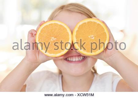 Young girl holding oranges over eyes. - Stock Photo