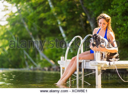 Young woman with dog sitting on jetty over lake - Stock Photo