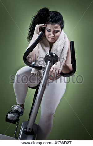 Woman using exercise bike at home - Stock Photo