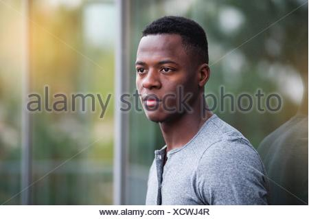 Portrait of young man, leaning against window, outdoors - Stock Photo