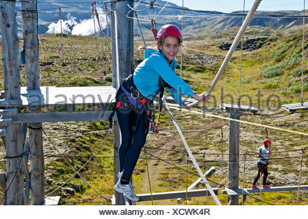 Teenage girl holding rope on high rope course - Stock Photo