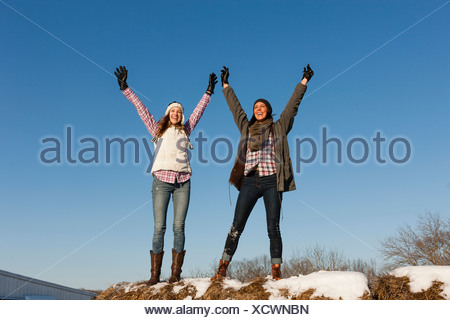 Two young women with arms raised on winter hilltop - Stock Photo