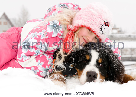 Bernese Mountain Dog (Canis lupus f. familiaris), girl lying with her dog in the snow - Stock Photo