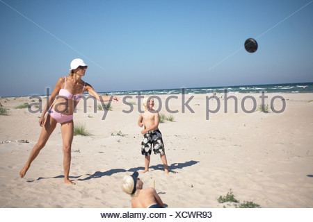 Mother and children playing on the beach. - Stock Photo