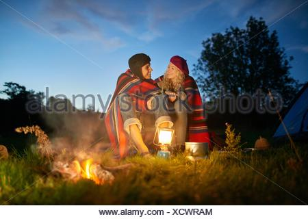 Young camping couple sitting by campfire at dusk - Stock Photo