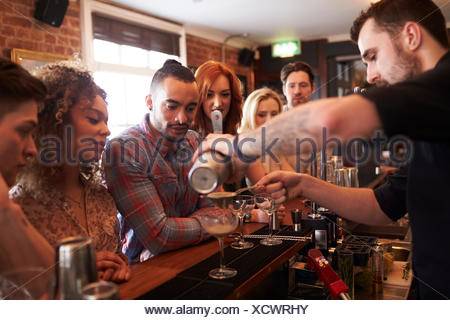 Bartender Giving Cocktail Making Lesson to Friends In Bar - Stock Photo