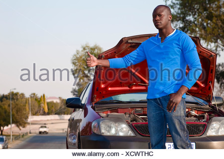 African man standing in front of his broken car, hitchhiking - Stock Photo