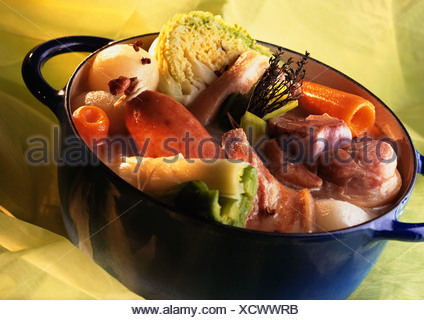 Blue cooking pot full of with meat and vegetables - Stock Photo