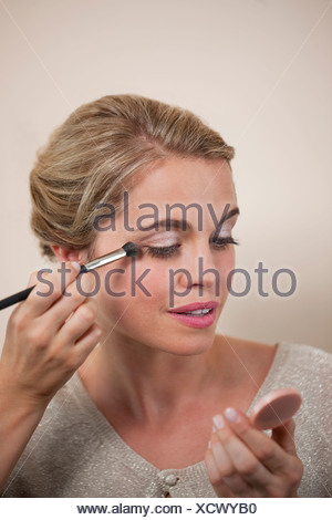 A young woman applying eye makeup - Stock Photo
