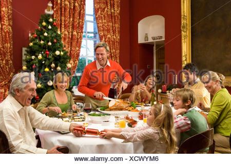 Three generation family and friends having Christmas dinner, - Stock Photo