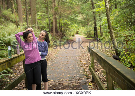 Daughter helping mother stretch preparing for run woods - Stock Photo