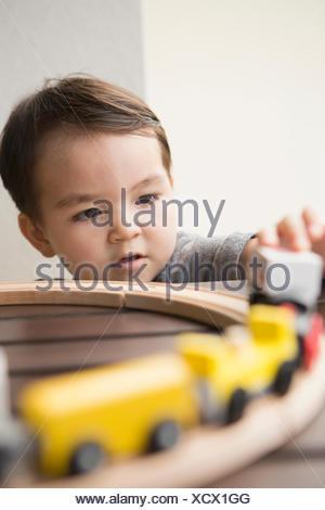 Young boy playing with a wooden train set. - Stock Photo