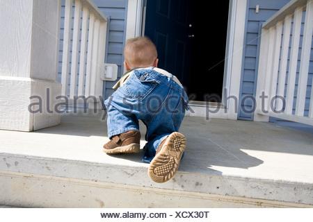 Child crawling towards open door - Stock Photo