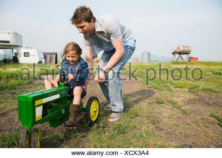 Father pushing daughter on toy tractor in field - Stock Photo