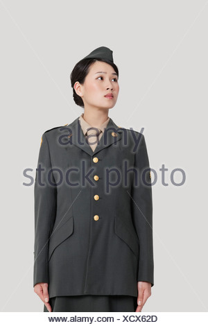 Female US military officer standing in attention as she looks away over gray background - Stock Photo