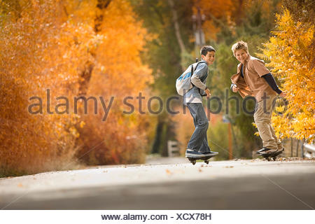 Two boys on skate boards on a roadway in woodland with vivid autumn foliage. - Stock Photo