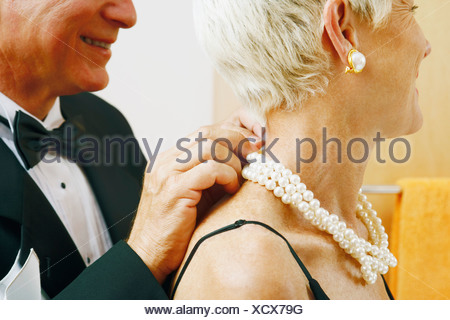 Close-up of a mature man putting a pearl necklace around a mature woman's neck - Stock Photo