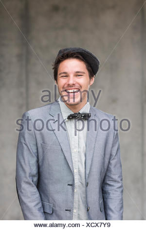 Young man wearing flat cap and bow tie, laughing - Stock Photo