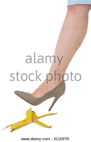 Cropped image of businesswoman crushing banana skin - Stock Photo