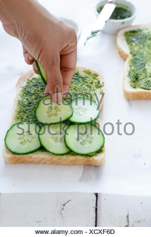 Placing Cucumber slices over spread coriander chutney on the bread. - Stock Photo