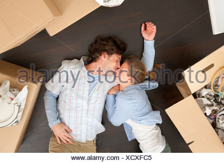Couple laying together on floor - Stock Photo