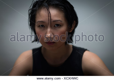 Close up studio portrait of serious young woman - Stock Photo