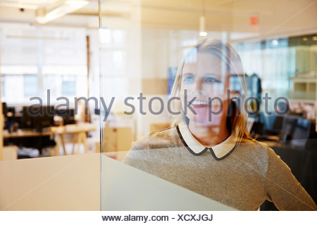 View through glass of female office worker - Stock Photo