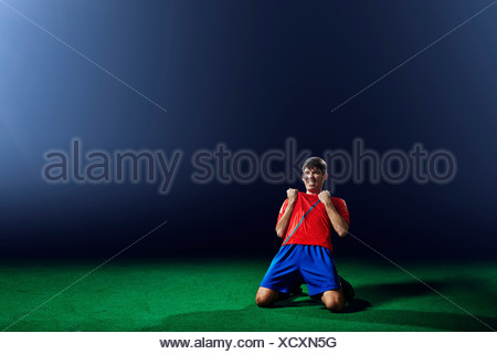 Male soccer player celebrating on knees - Stock Photo