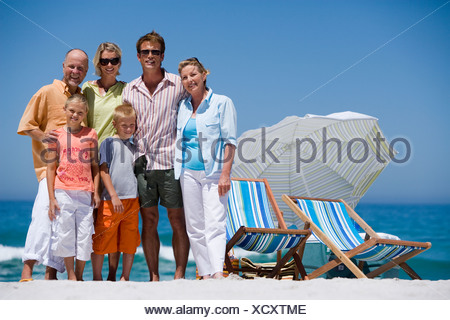 Multi generational family standing on beach beside deckchairs smiling front view portrait - Stock Photo