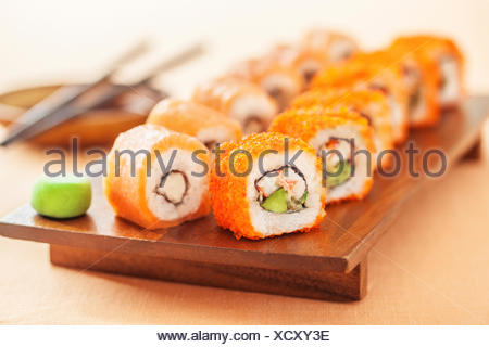 California and Alaska rolls on a wooden plate - Stock Photo