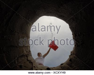 Directly Below Shot Of Young Woman Pouring Water In Hole - Stock Photo