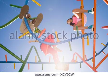 Children sitting on monkey bars at playground - Stock Photo