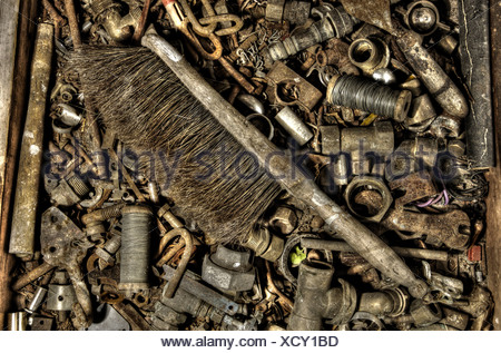 An old hand brush in a box of old nuts and bolts - Stock Photo
