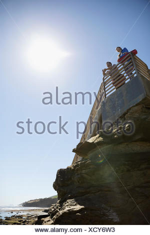 Man and woman with yoga mats on stairs above craggy sunny beach - Stock Photo