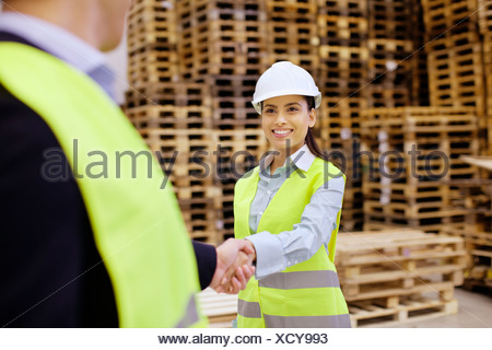 Supervisor and trainee shaking hands in distribution warehouse - Stock Photo