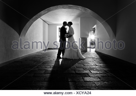 Bride and groom kissing under the arch of an old vault, Rattenberg, Tyrol, Austria - Stock Photo