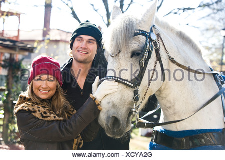 Portrait of young couple in warm clothing standing with horse - Stock Photo