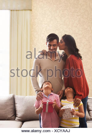 Woman kissing man on cheek, girl and boy holding gifts looking up with heads back - Stock Photo