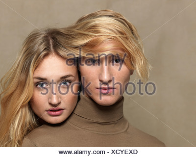 Young woman covering man's head with long blonde hair - Stock Photo