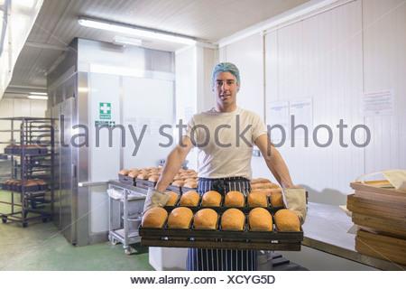 Baker holding tray of freshly baked bread, portrait - Stock Photo