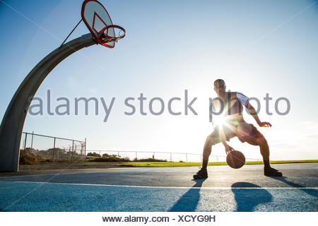 Young man playing basketball in a park, Los Angeles, California, USA - Stock Photo