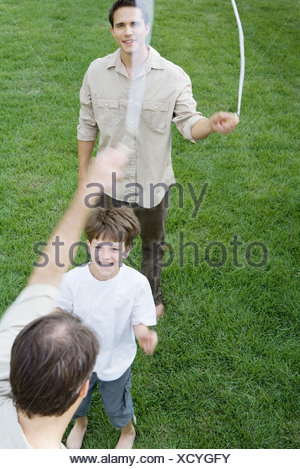 Boy playing jump rope with two men, smiling, cropped view - Stock Photo