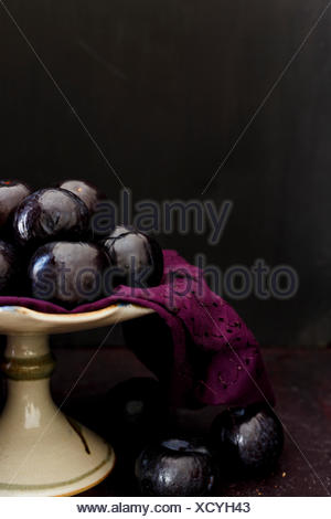 Whole Plums on a Cake Stand - Stock Photo