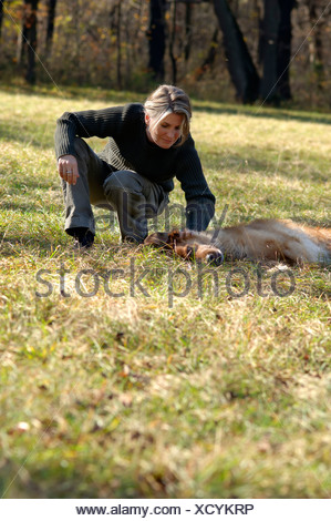 Woman plays with lying dog - Stock Photo