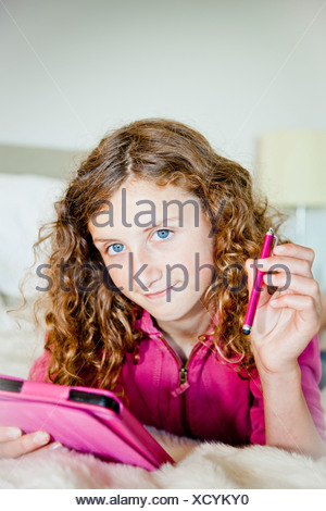 Teen girl on bed with tablet - Stock Photo