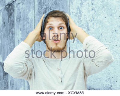 Portrait of a young man with a beard, woolly hat, standing in front of a wall, looking amazed - Stock Photo