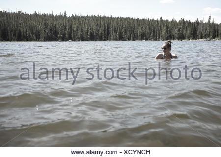 USA, Wyoming, Woman swimming in mountain lake - Stock Photo