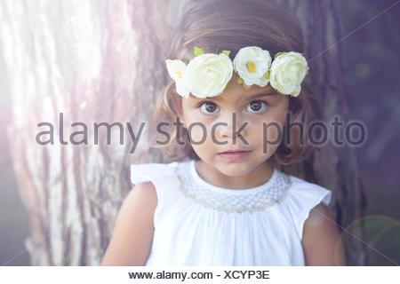 Portrait of a smiling girl wearing a flower headdress - Stock Photo