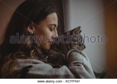 Close-up of beautiful woman smelling her pet cat - Stock Photo
